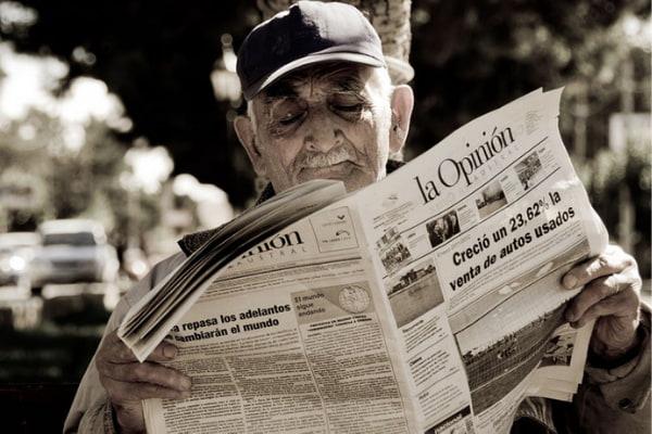 Old man wearing cap reading news paper