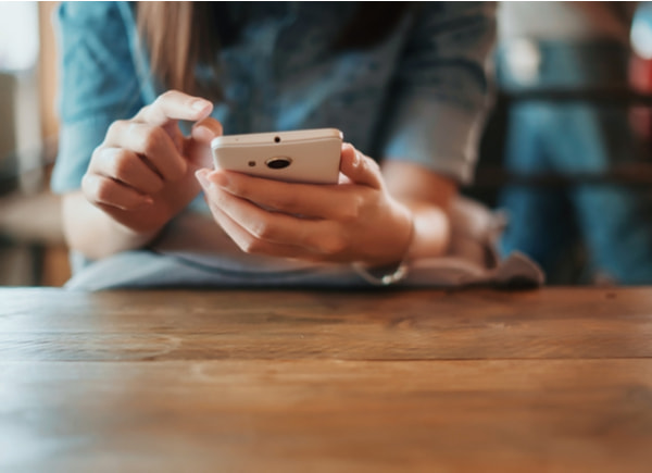Woman using smartphone on wooden table