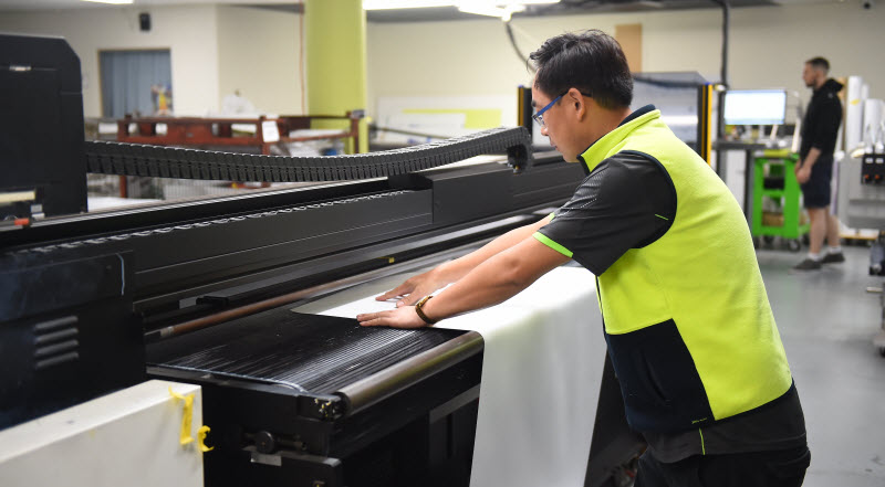 Man holding the tarpaulin in the machine