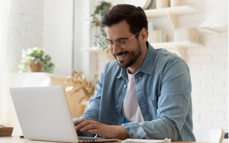 Man smiling while in front of the laptop